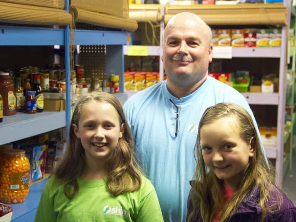 Mt. Lebanon residents Madi Senneway, left, and Eva Schmidt, pictured in South Hills Interfaith Movement's Bethel Park food pantry with executive director Jim Guffey, have raised money toward the organization's efforts at helping the needy.
