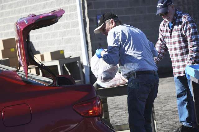 Volunteers help load groceries into cars