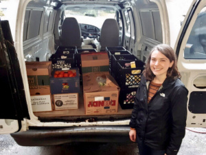 Woman posed in front of van of donations