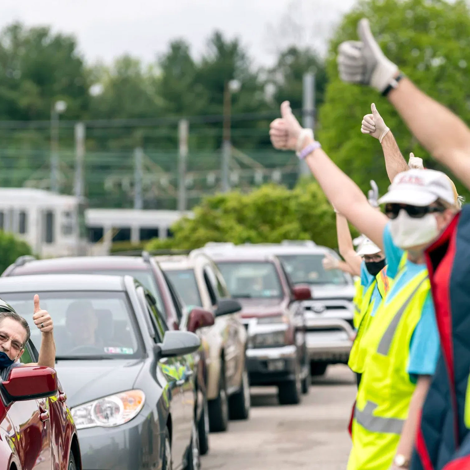 A recipient gives a thumbs up with volunteers
