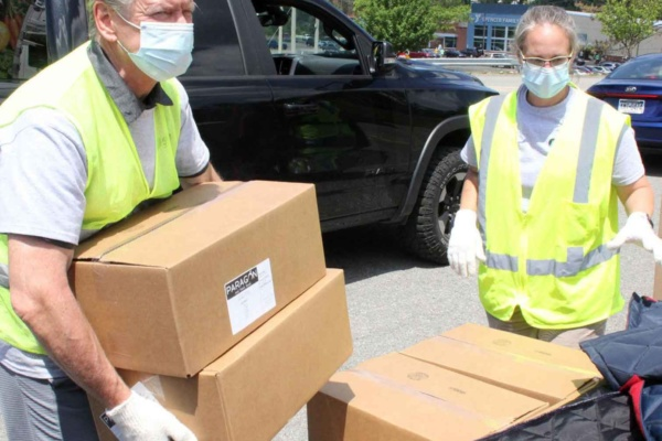 Volunteers load boxes of food during food distribution