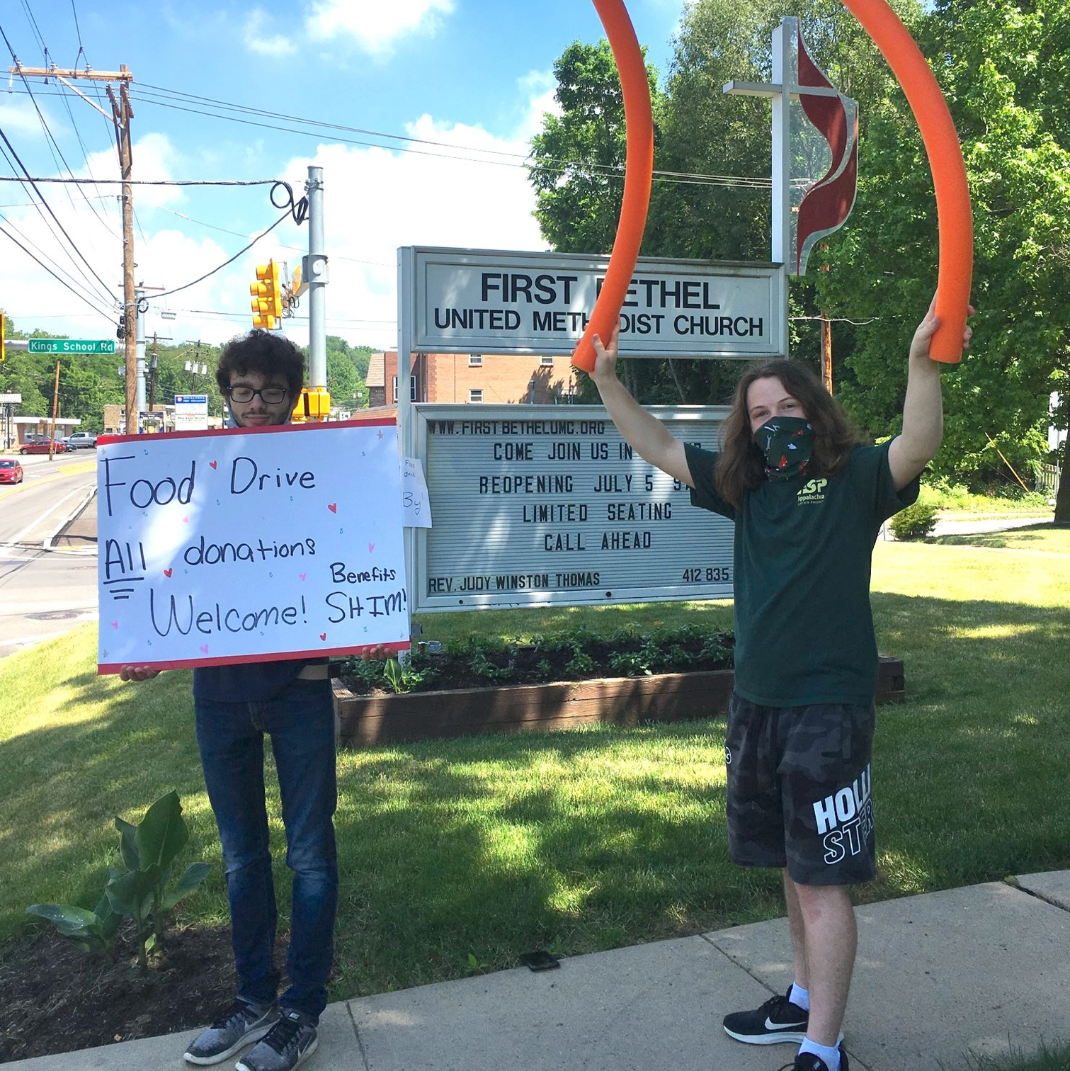 Teens hold up sign for food drive
