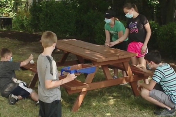 Students are painting the picnic tables here at SHIM