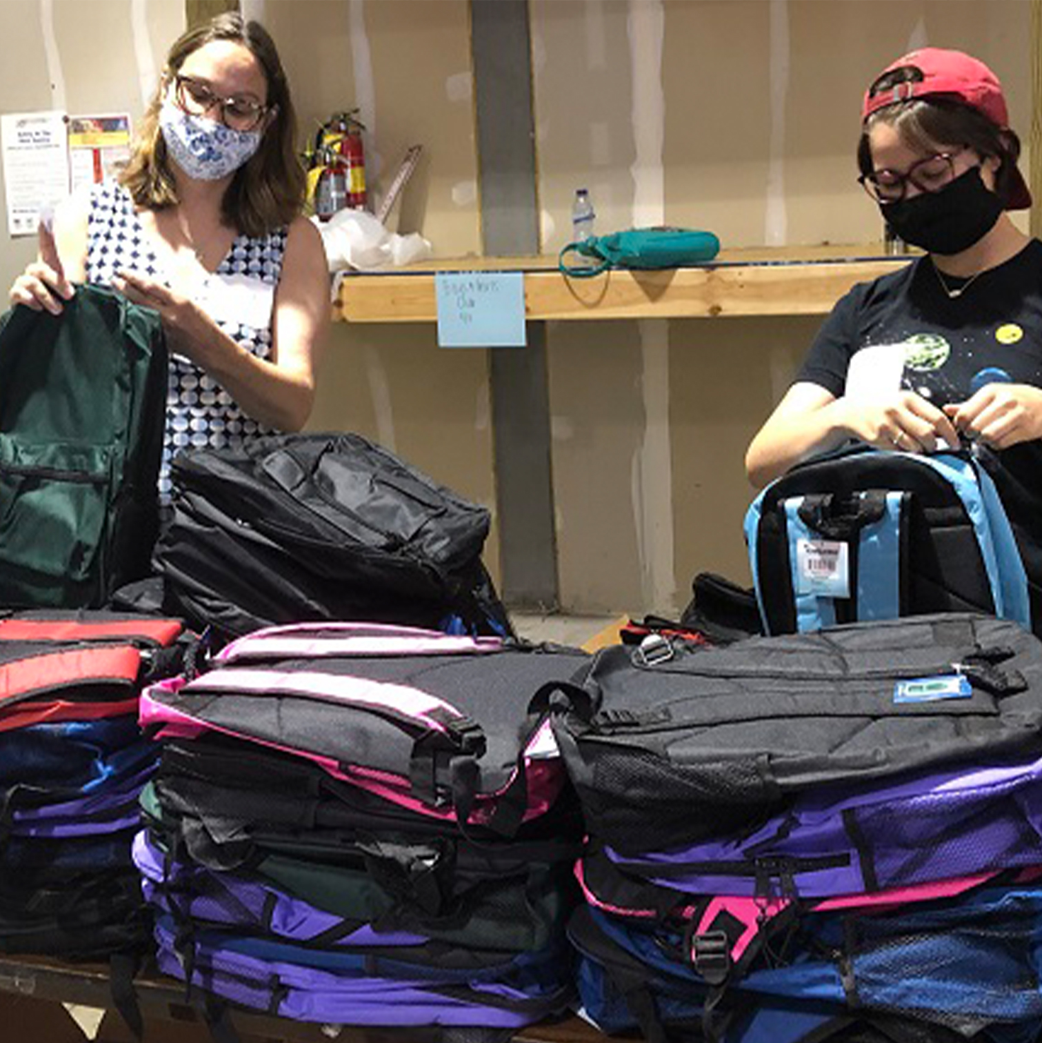 Helpers pack bookbags for back-to-school