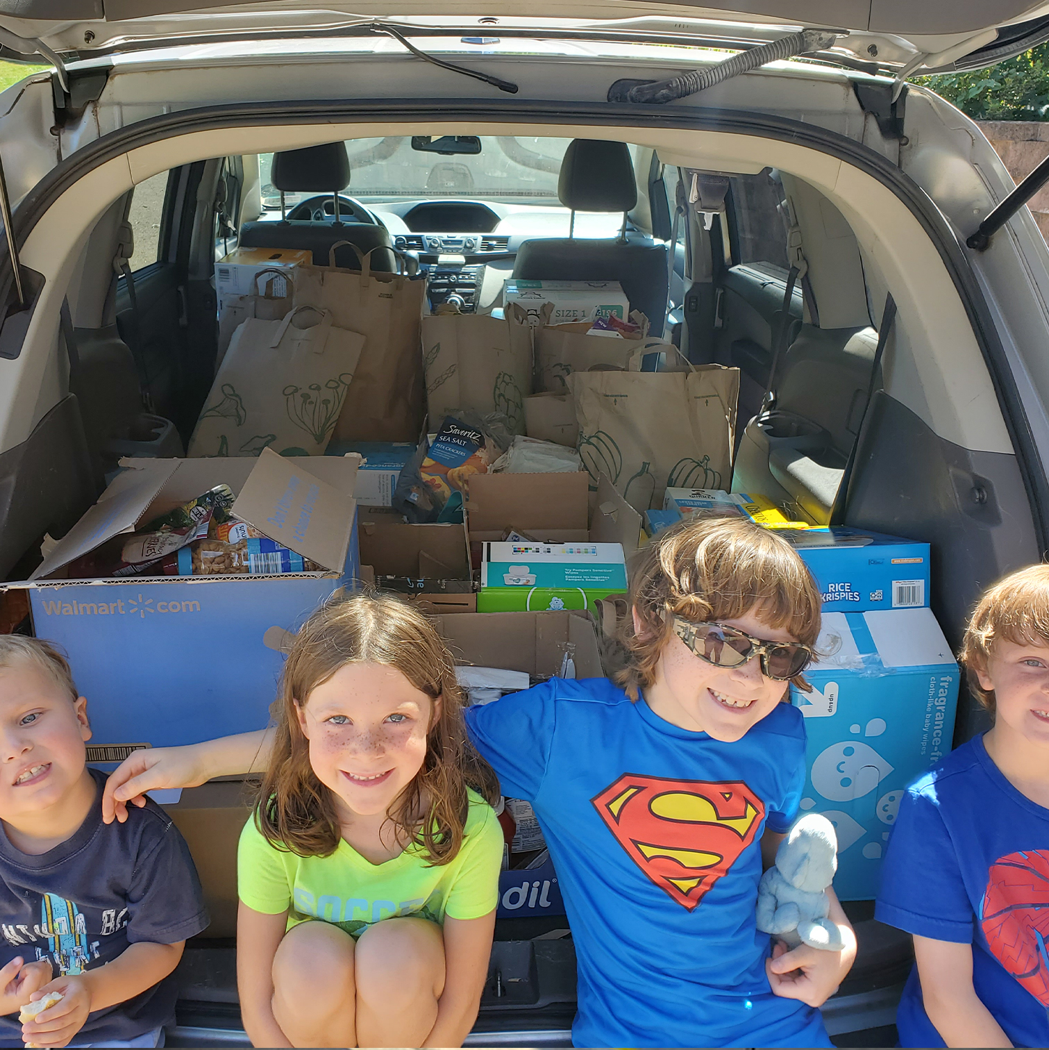 4 youth posing in front of a car load of donations