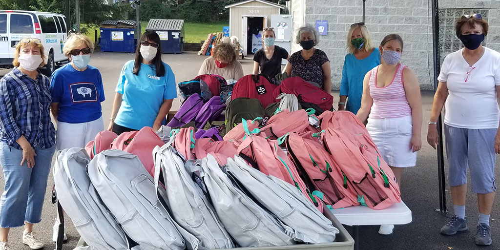 Group of volunteers distributing book bags for back to school