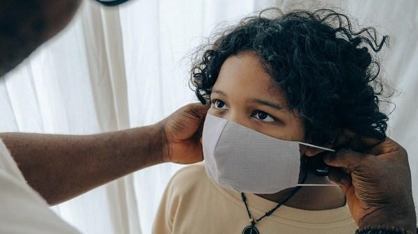 Adult puts mask on child