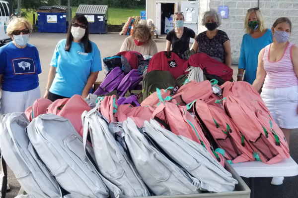 Group of volunteers with book bag donations