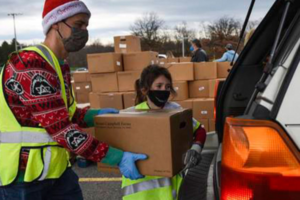 Volunteers load cars during SHIM's food distribution