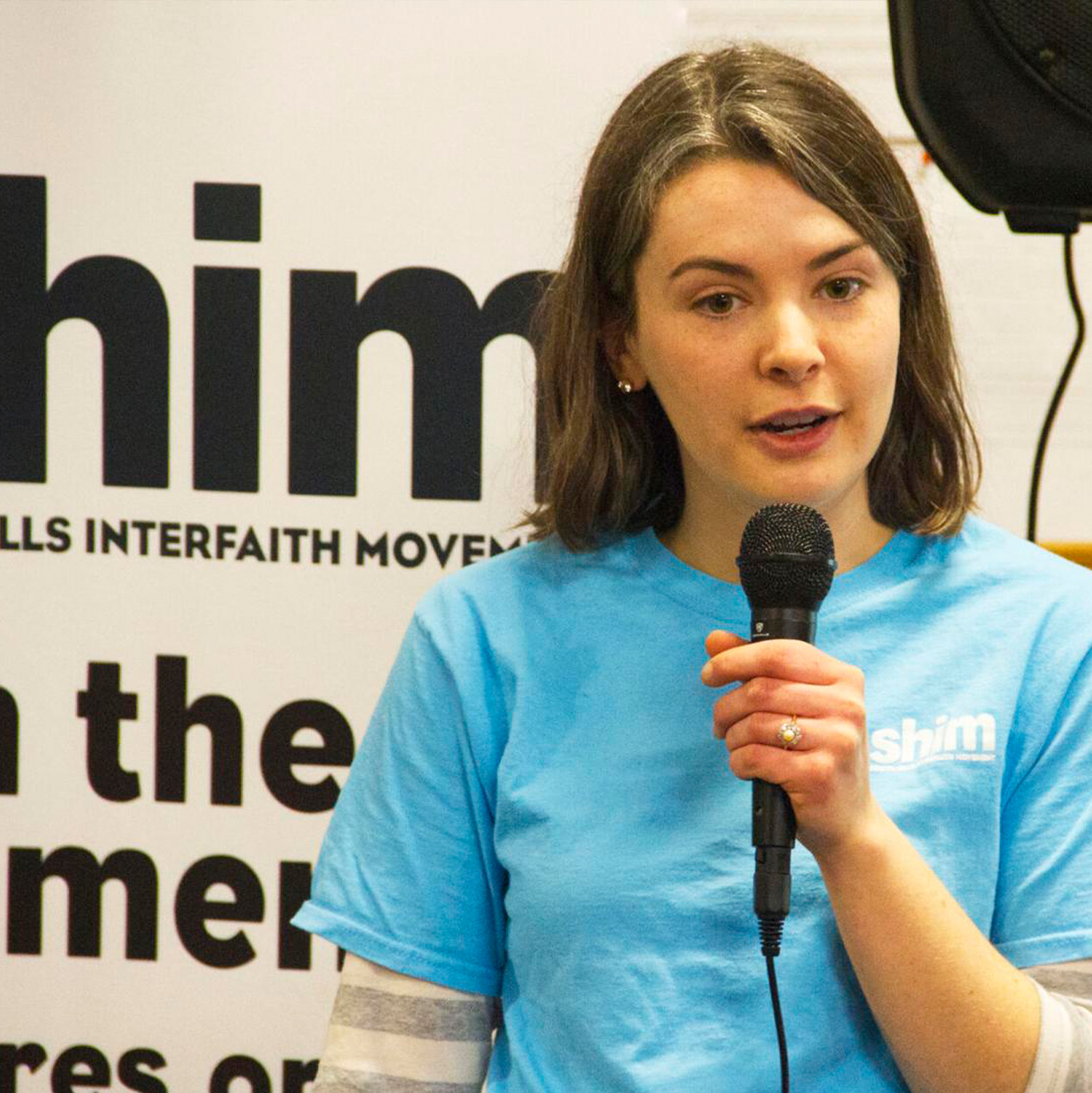 Molly Penderville holds microphone and speaks about Sack Hunger at SHIM